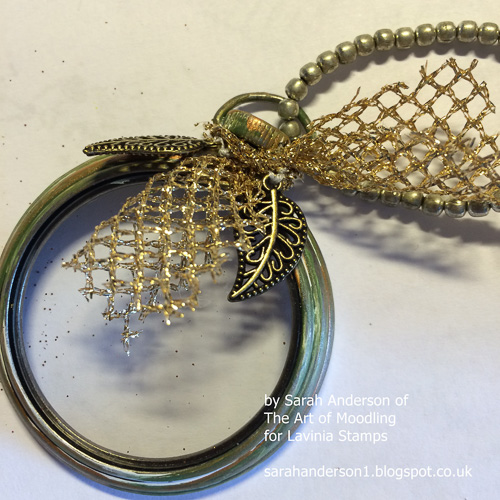 Tie a short piece of fabric or ribbon to the pocket watch and add some charms.